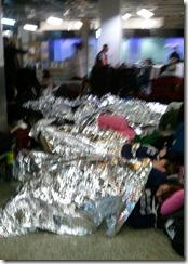 People sleeping in Heathrow T3 with space blankets from Virgin Atlantic